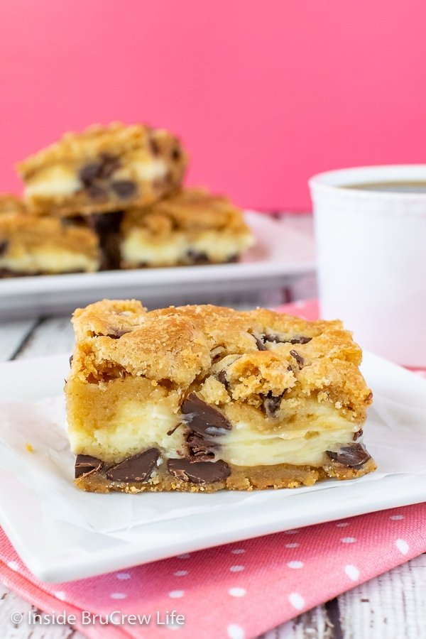 A white plate with a square of chocolate chip cheesecake bars on it with more bars behind it.