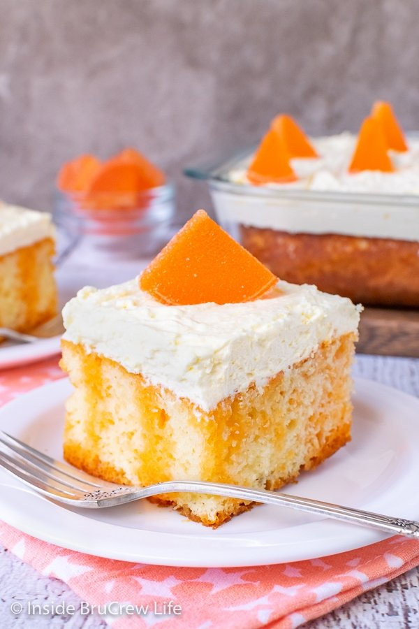 A square of vanilla cake with orange Jello stripes topped with vanilla pudding frosting and an orange slice