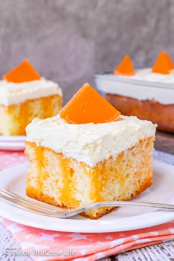 Two white plates with pieces of orange creamsicle cake topped with vanilla mousse frosting and orange slices