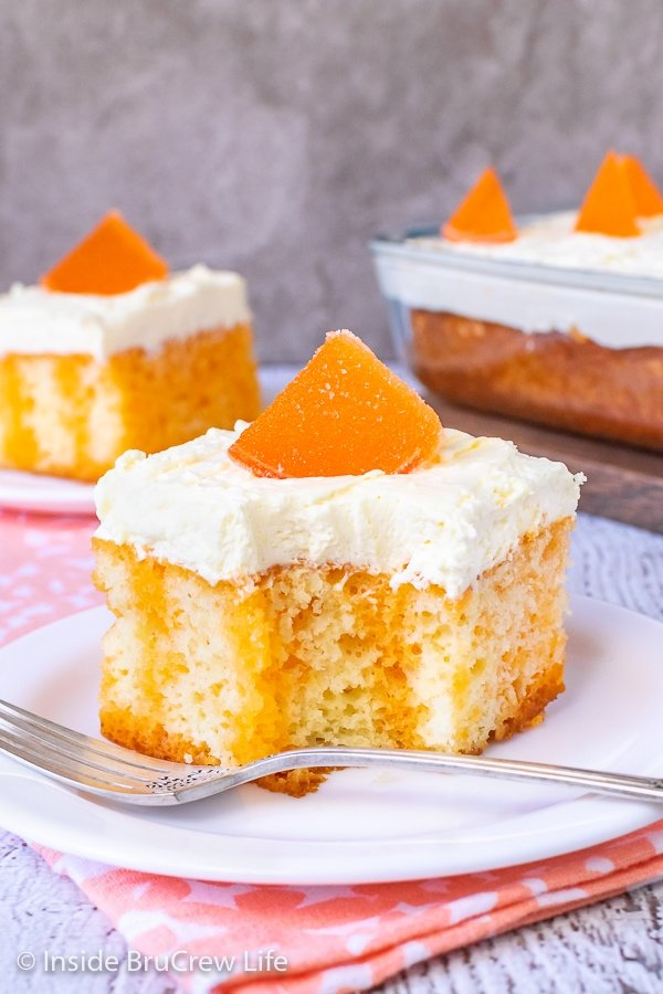 Two white plates with pieces of orange creamsicle cake topped with vanilla pudding frosting and orange slices on them