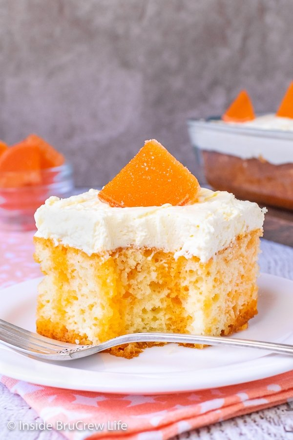 A white plate with a piece of orange creamsicle cake topped with a vanilla pudding frosting and an orange slice on it