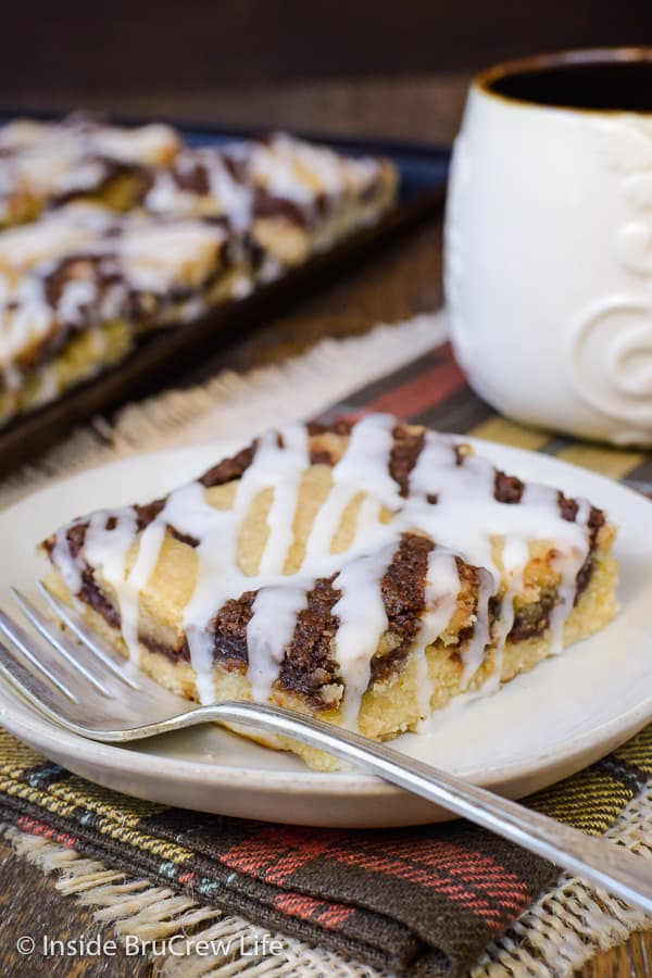 Banana Nutella Snack Cake - a soft banana cake with Nutella cheesecake and a sweet glaze is a delicious treat to start the day with. Make this easy recipe for breakfast or brunch and watch it disappear. #bananacake #breakfast #brunch #Nutella #banana #egglessrecipe #eggfree