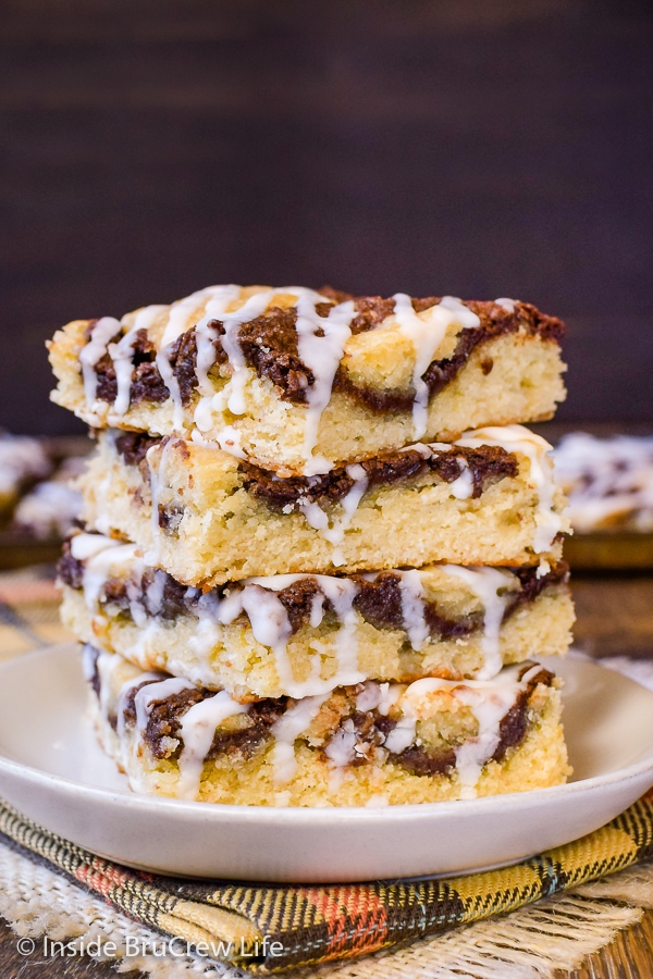 Stack of four banana nutella snack cake squares on a cream plate