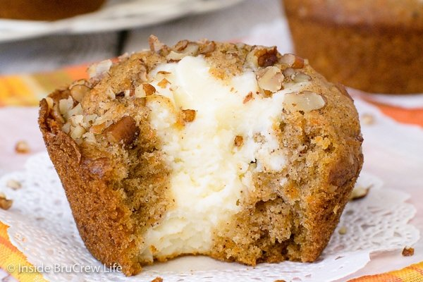 A carrot cheesecake muffin with a bite out of it on a white paper