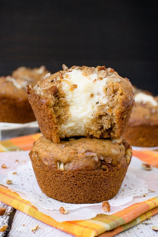 Two carrot cake muffins stacked on top of each other on an orange towel with a bite taken out of the top one showing the cheesecake center