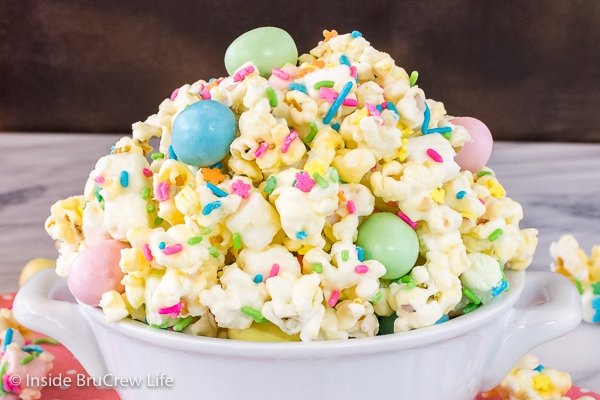 A close up picture of a white bowl filled with white chocolate popcorn with candy and sprinkles in it