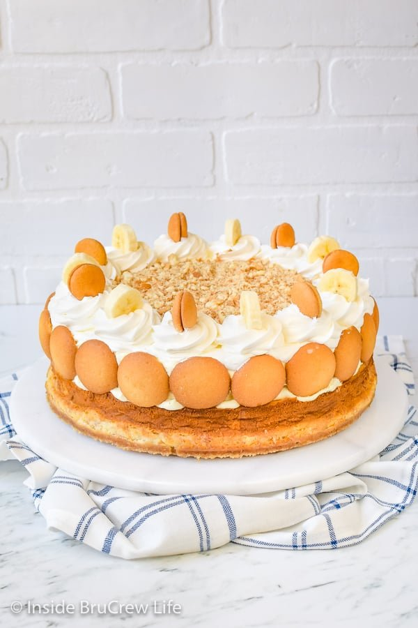 A full sized banana cheesecake topped with banana pudding on a white cake plate.