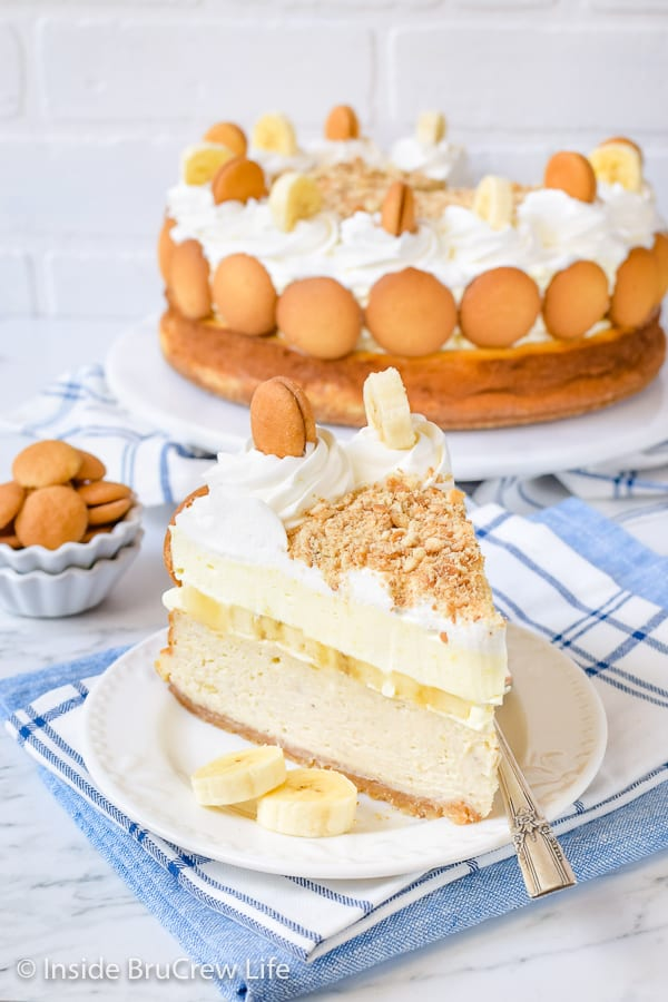 A slice of banana pudding cheesecake on a white plate with more cheesecake behind it.