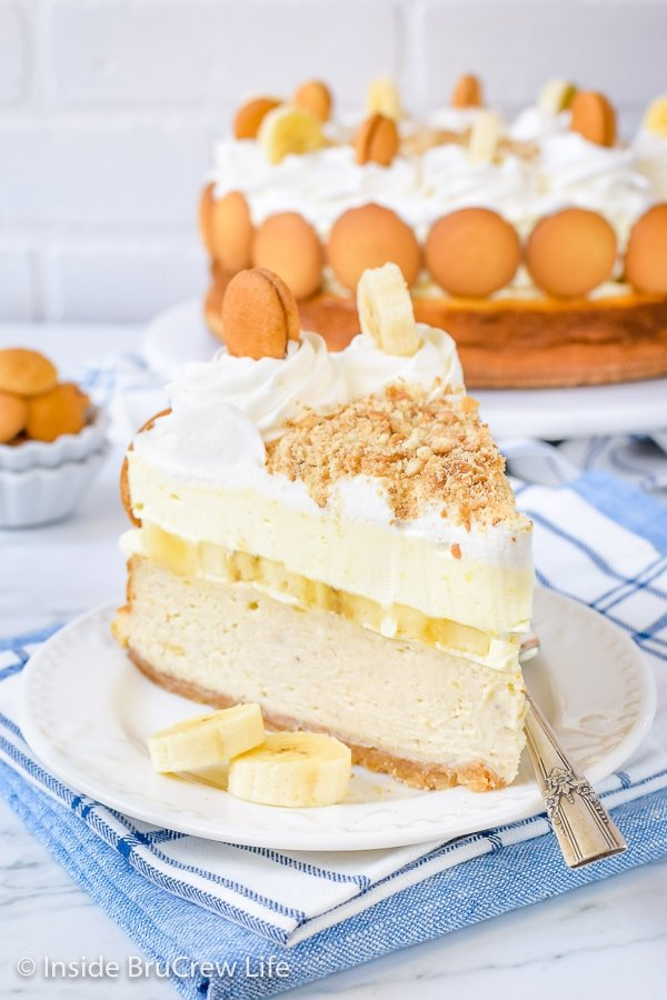 A white plate with a slice of Banana Pudding Cheesecake on it and the rest behind it.