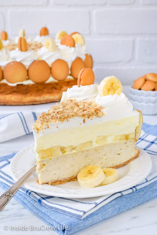 A white plate with a slice of banana pudding cheesecake and a fork on it.