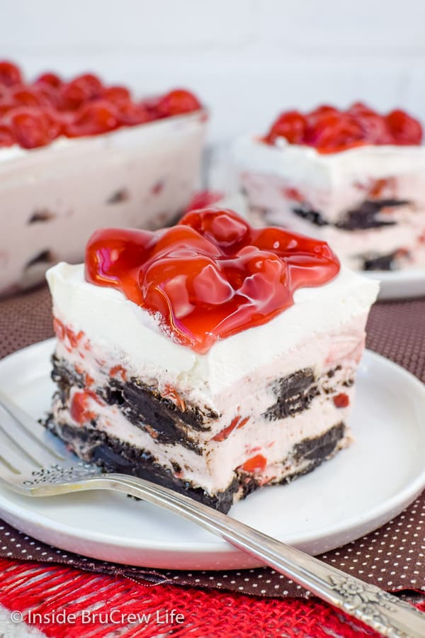 Two white plates on a brown towel with squares of cherry oreo icebox cake on them and cherry pie filling on top