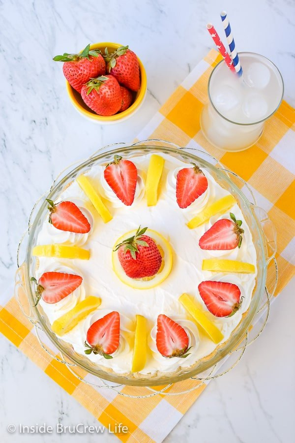 Overhead picture of the top of a lemon cream strawberry pie on a yellow and white towel