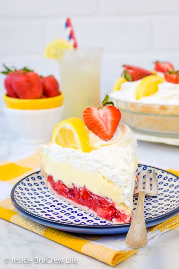 A blue and white plate with a slice of lemon cream strawberry pie on it
