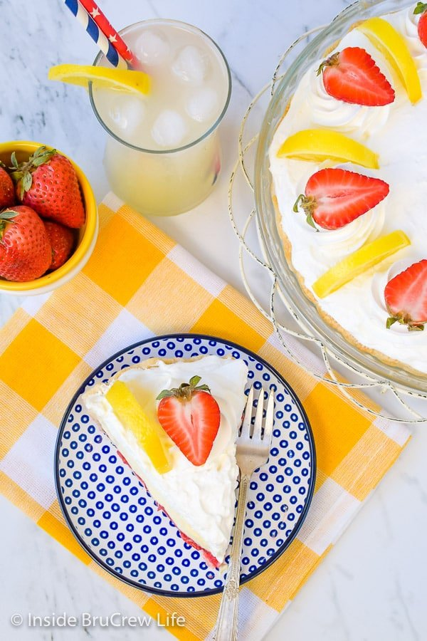 Overhead picture of a blue and white plate with a piece of lemon cream strawberry pie on it and pie plate