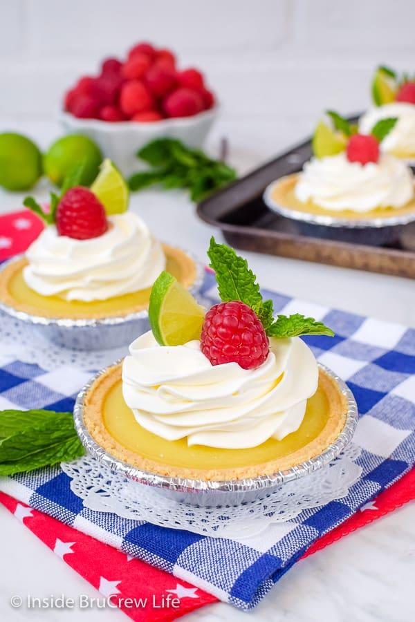 No Bake Mini Key Lime Pies - an easy key lime curd inside graham cracker crusts makes an easy dessert. Make this no bake recipe during the hot summer months! #nobake #keylime #keylimepie #easyrecipe #pie #keylimecurd