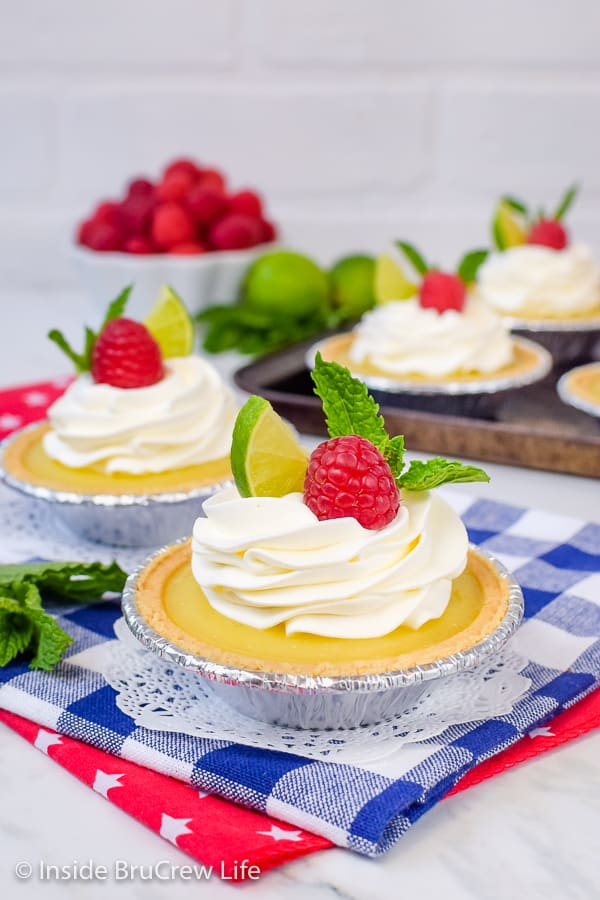 No Bake Mini Key Lime Pies - homemade key lime curd inside mini graham cracker crusts make the perfect summer dessert. Make this easy no bake recipe for parties and picnics this summer! #nobake #keylime #keylimepie #easyrecipe #pie #keylimecurd