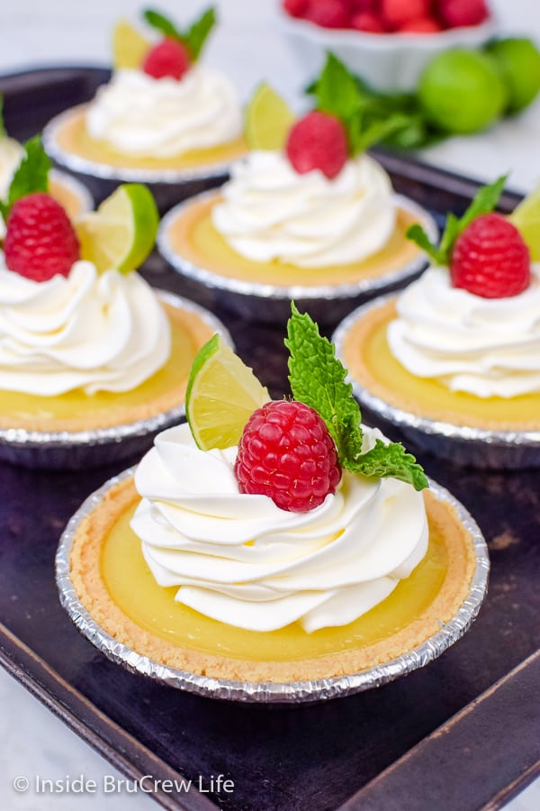 No Bake Mini Key Lime Pies - graham cracker crusts filled with homemade key lime curd are an easy dessert to make for summer parties and picnics! #nobake #keylime #keylimepie #easyrecipe #pie #keylimecurd