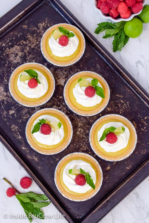 No Bake Mini Key Lime Pies - fill store bought graham cracker crusts with this easy key lime curd to make the cutest and easiest summer dessert! Great recipe for picnics and parties! #nobake #keylime #keylimepie #easyrecipe #pie #keylimecurd