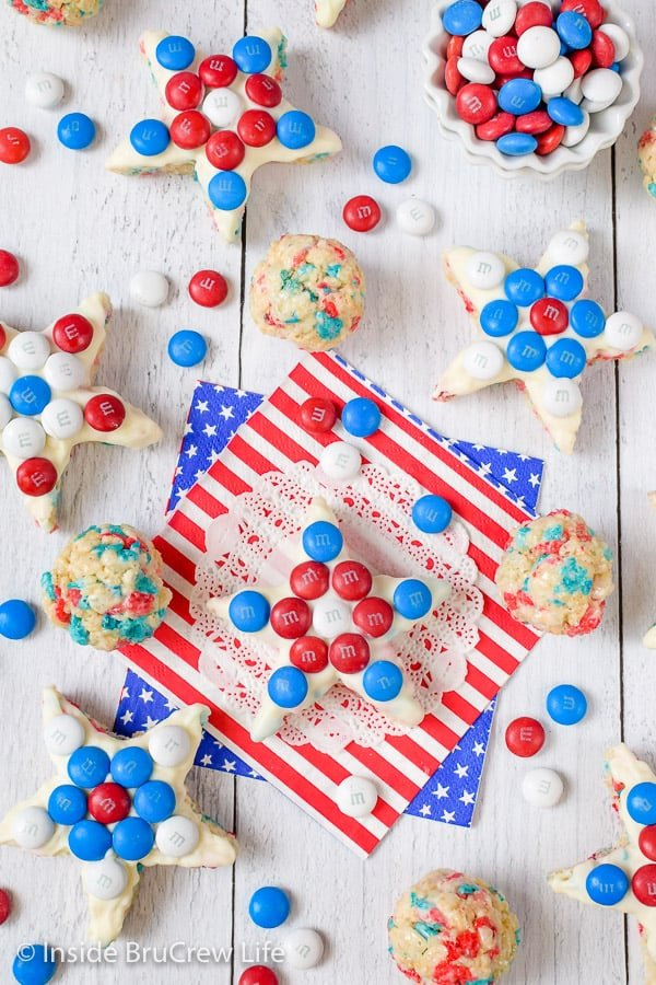 A white board with rice krispie treat stars topped with red white and blue m&m's on it
