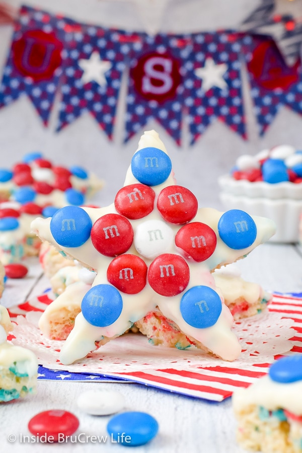 A rice krispie treat star decorated with white chocolate and red white and blue M&M candies standing up on a white board