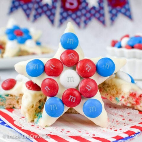 A star shaped rice krispie treat decorated with red white and blue M&M's standing up.