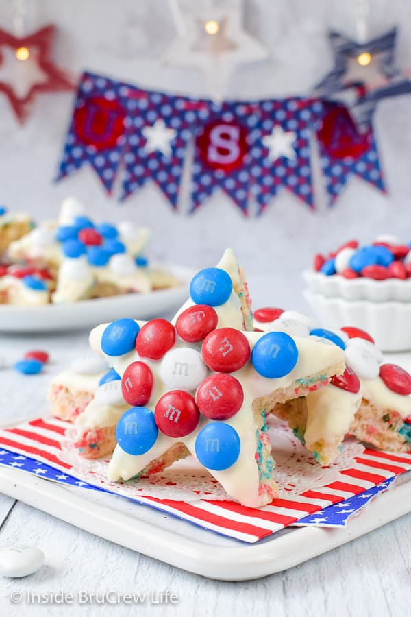 Rice krispie treat stars decorated with red white and blue M&M candies on a white board