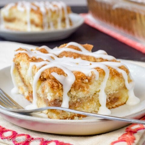 A white plate with a slice of sour cream coffee cake with a drizzle of glaze on it.