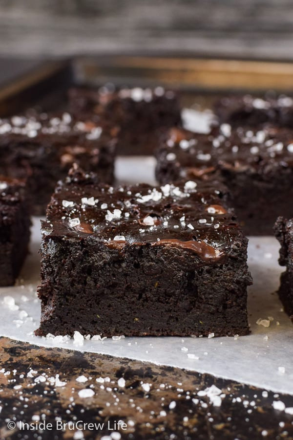 Close up picture of a dark chocolate zucchini brownie on a tray with more brownies behind it