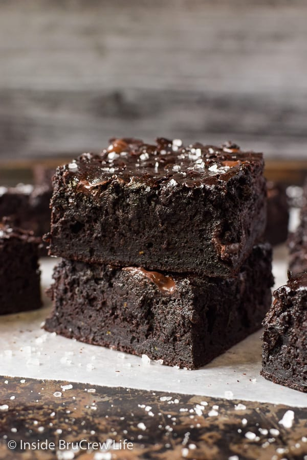 Two chocolate zucchini brownies stack on top of each other and sprinkled with sea salt