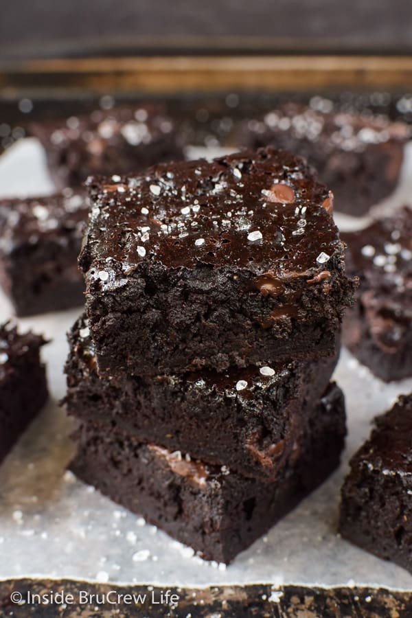 Three chocolate zucchini brownies stacked together with more brownies all around it