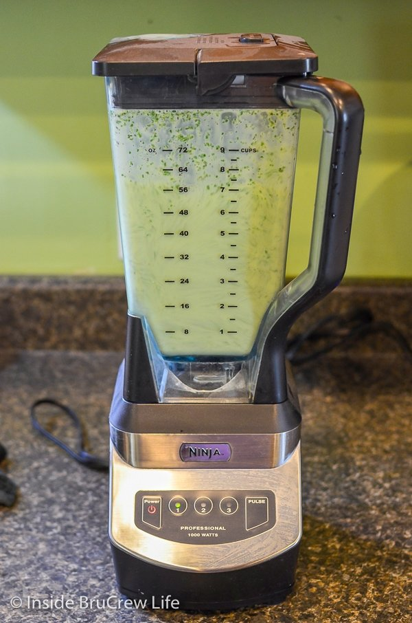 A blender filled with a green sauce for chicken enchiladas