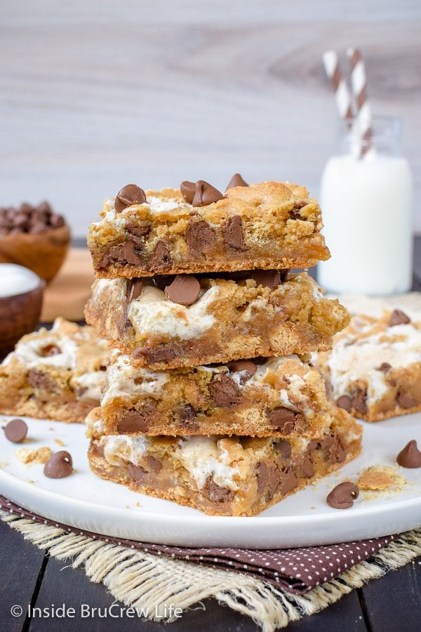 A white plate with a stack of s'mores blondies on it.