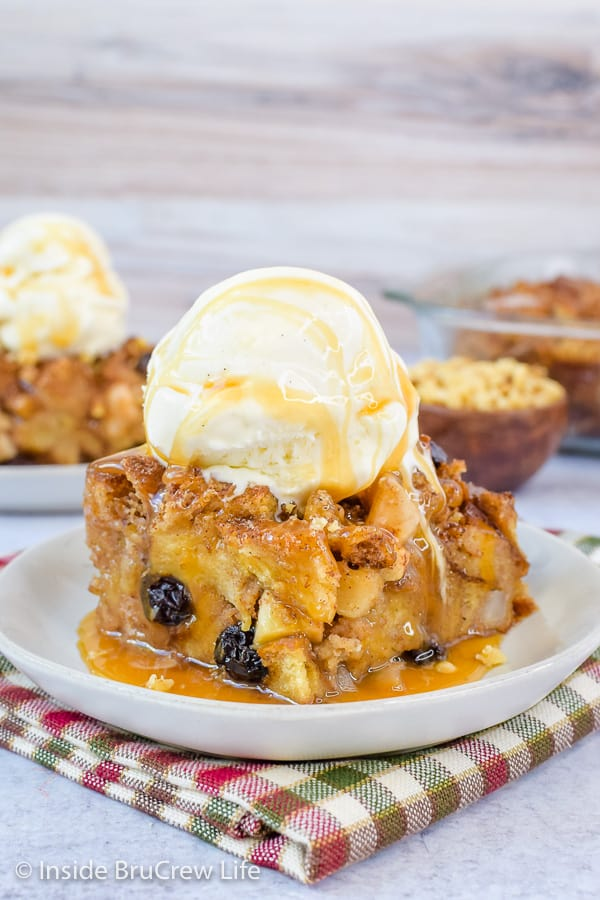 A square of apple bread pudding topped with ice cream and caramel on a white plate
