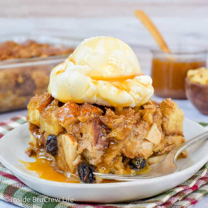 A white plate with a square of bread pudding with apples and raisins topped with ice cream on it