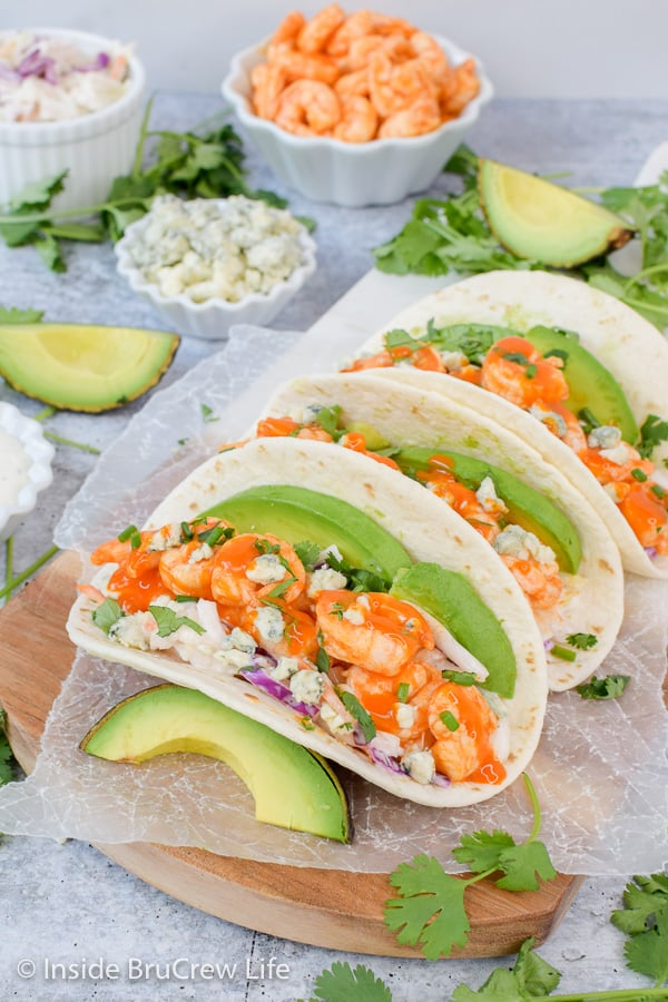 Easy Buffalo Shrimp Tacos - these easy shrimp tacos are loaded with toppings and drizzled with wing sauce. Great recipe to make on busy nights! #tacos #buffaloshrimp #shrimptacos #tacotuesday