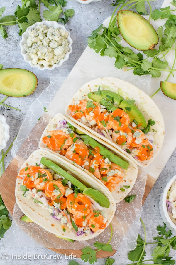 Easy Buffalo Shrimp Tacos - lots of toppings and buffalo shrimp make these easy shrimp tacos a win at the dinner table. Make this easy recipe on busy nights! #tacos #buffaloshrimp #shrimptacos #tacotuesday