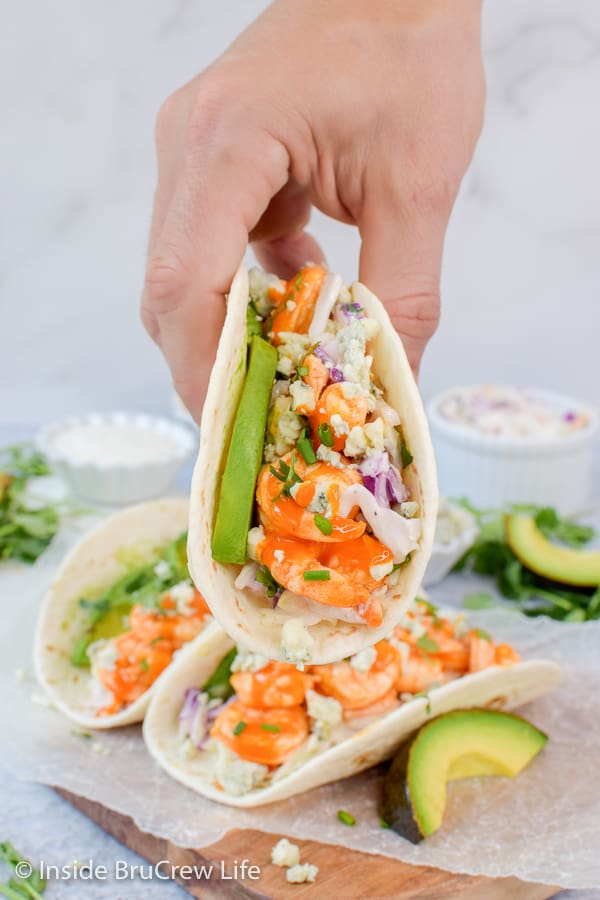 Easy Buffalo Shrimp Tacos - tortillas stuffed with toppings and buffalo shrimp will make everyone happy at the dinner table. Make this easy recipe on busy nights! #tacos #buffaloshrimp #shrimptacos #tacotuesday