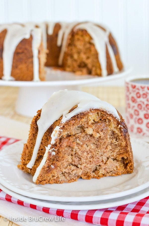 A white plate with a slice of apple bundt cake drizzled with apple cider glaze on top and the cake behind it.