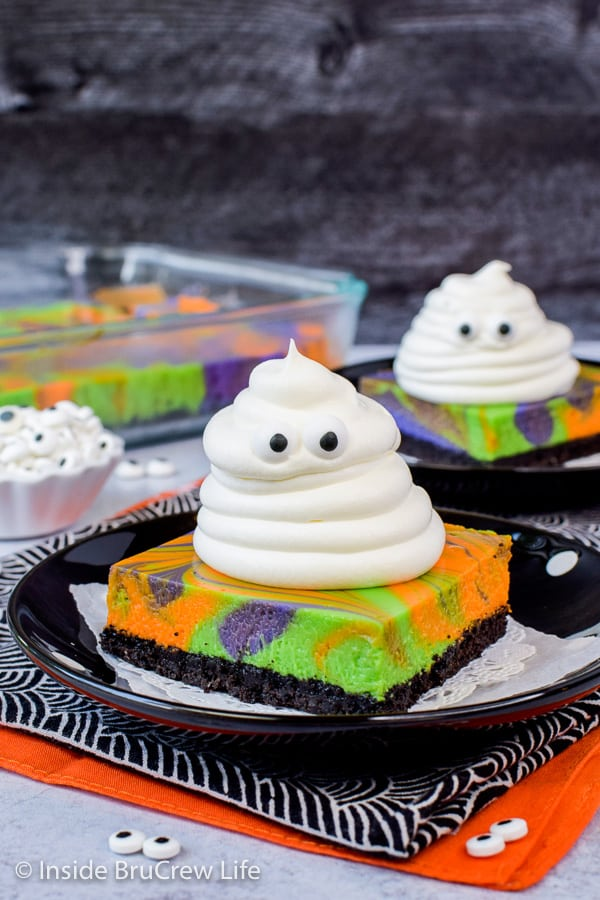 Halloween Swirled Cheesecake Bars - spooky whipped cream ghosts and colorful swirled cheesecake bars are a fun dessert. Make this easy recipe for Halloween parties. #cheesecake #halloween #ghosts #cheesecakebars