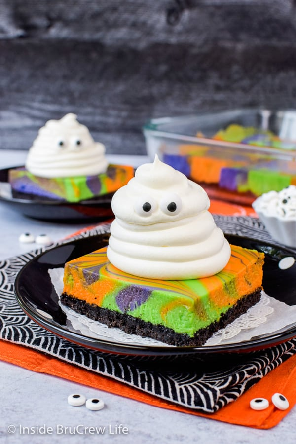Halloween Swirled Cheesecake Bars - whipped cream ghosts and colorful cheesecake swirls make this dessert disappear in a hurry. Great recipe to make for Halloween parties. #cheesecake #halloween #ghosts #cheesecakebars