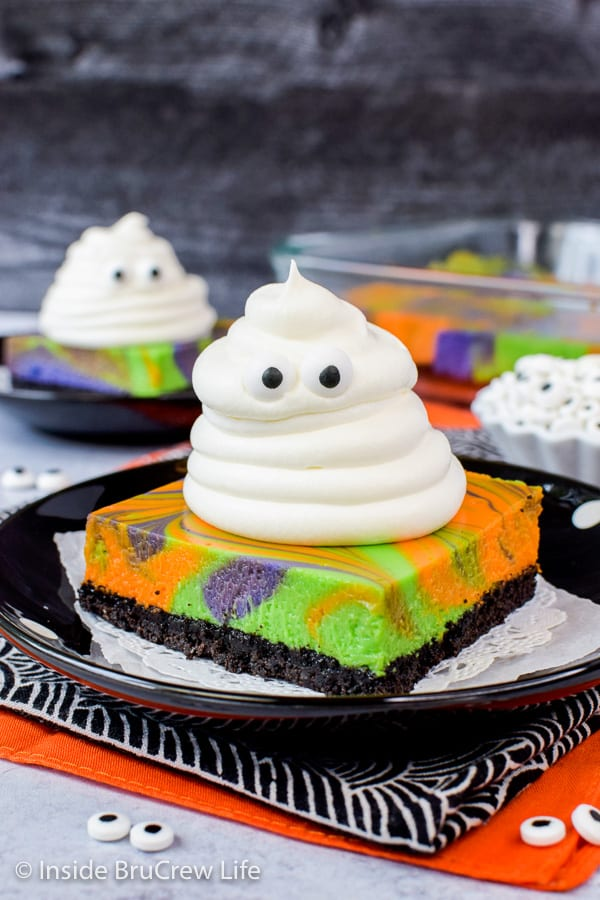 Halloween Swirled Cheesecake Bars - an Oreo crust, colorful cheesecake swirls, and a spooky whipped cream ghost make these a fun Halloween dessert. Make this easy recipe for fall parties. #cheesecake #halloween #ghosts #cheesecakebars