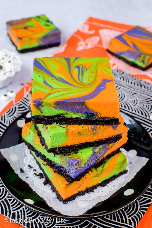Halloween Swirled Cheesecake Bars - swirls of colors make these cheesecake bars a fun treat for every holiday. Make this easy recipe for Halloween parties. #cheesecake #halloween #ghosts #cheesecakebars