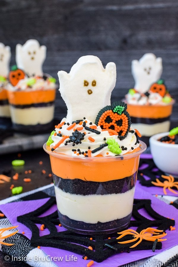 A clear cup with layers of white and orange no bake cheesecake and Oreo crumbs. Cool Whip, ghost marshmallow, and sprinkles are on top.