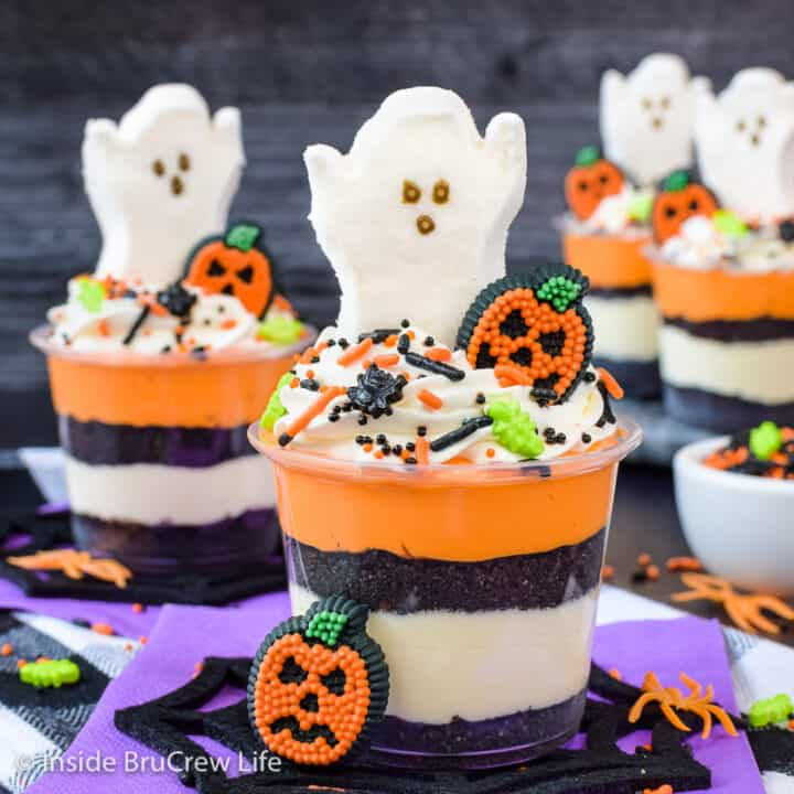 Clear cups filled with layers of vanilla cheesecake and Oreo cookie crumbs and topped with a ghost peep.
