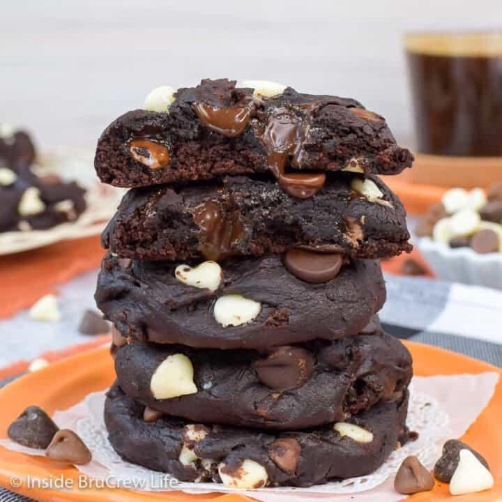 A stack of dark chocolate pumpkin cookies on an orange plate.
