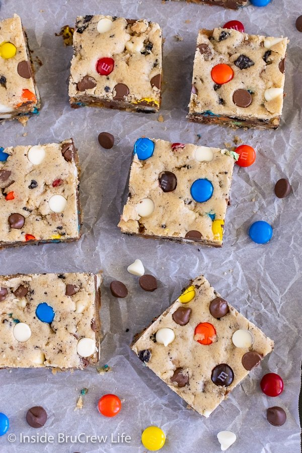 Overhead picture of squares of blondies loaded with candy, chocolate chips, and cookies on a piece of parchment paper