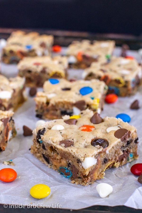 Squares of blonde brownies filled with chocolate, candy, and cookies on a sheet pan