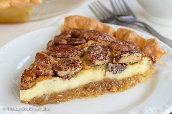 A slice of pecan cheesecake pie on a white plate with two forks behind it.