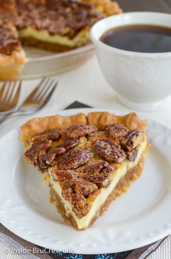A slice of cheesecake pecan pie on a white plate with a cup of coffee behind it.