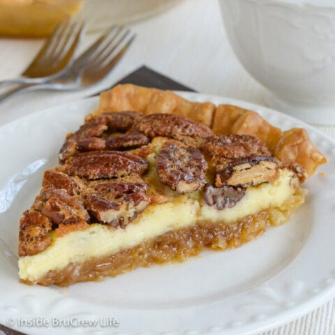 A white plate with a slice of pecan pie cheesecake on it.